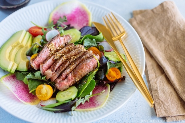Steak Salad with Shoyu Dressing on a white plate.