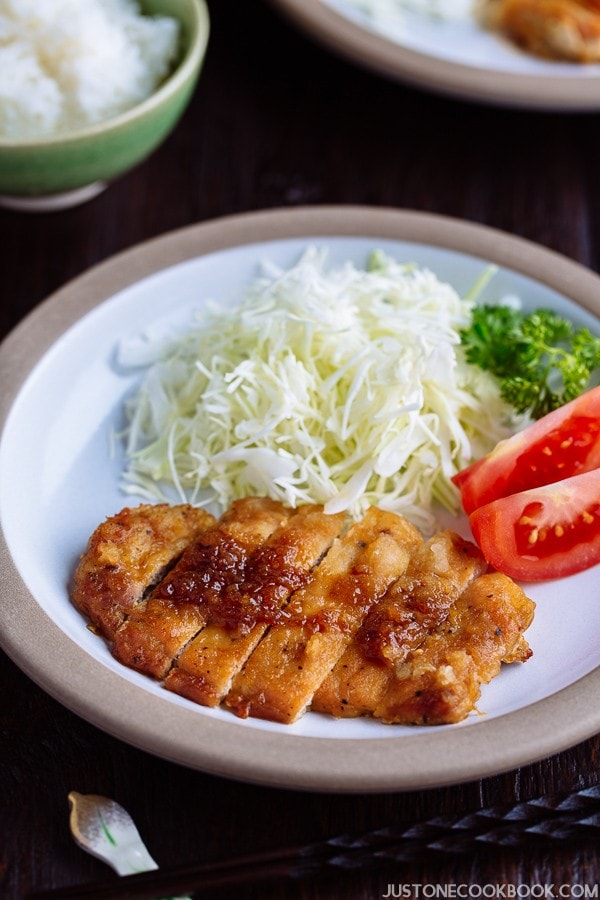 Tonteki, Japanese Pork Steak with cabbage and tomato salad on a plate.