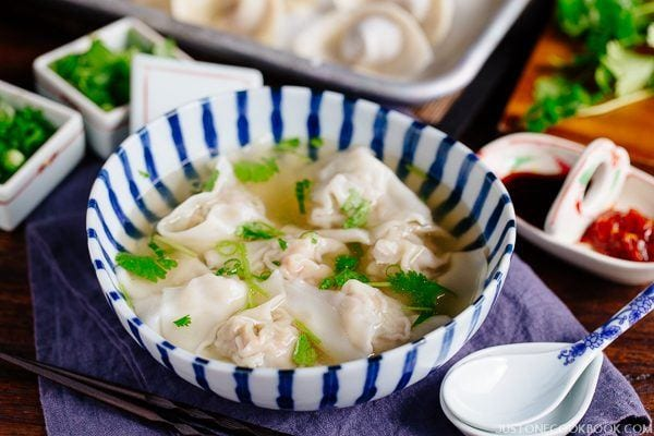 Shrimp and Pork Wonton Soup in a bowl and garnishes on a side.