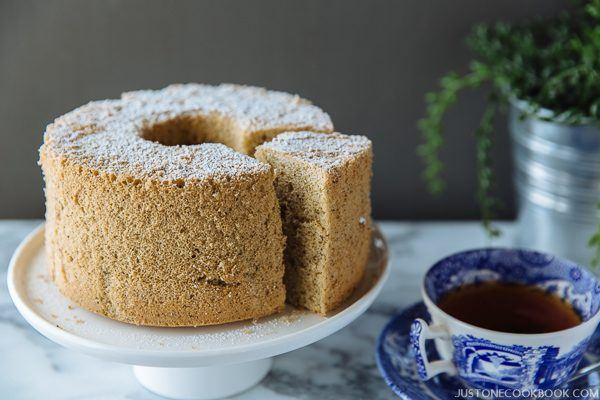 Earl Grey Chiffon Cake on a white cake stand with cup of tea.