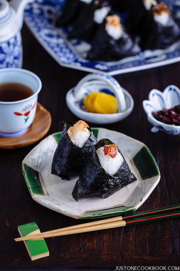 Onigiri on a small plate with tea and pickled on the side.