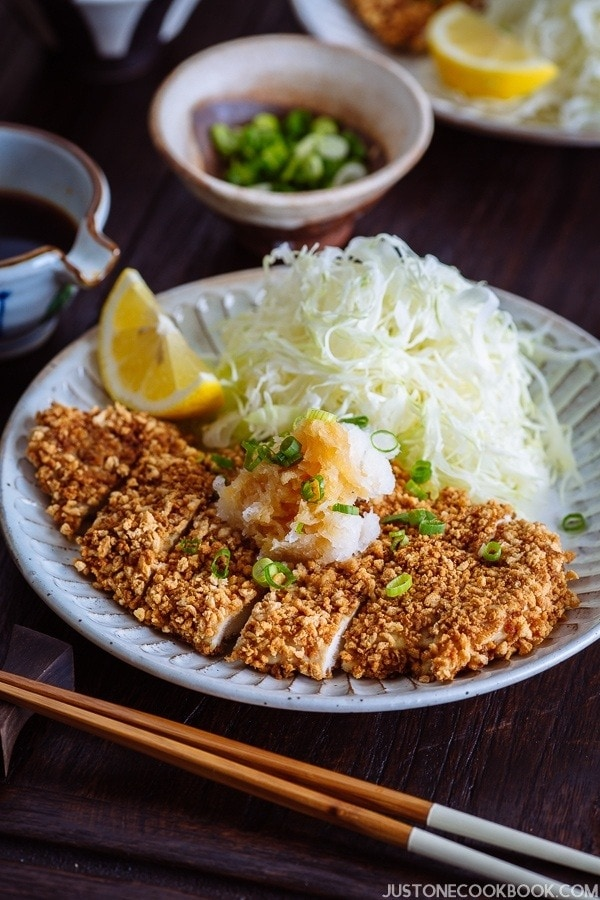 Gluten Free Baked Chicken Katsu with cabbage salad and sliced lemon on the plate.