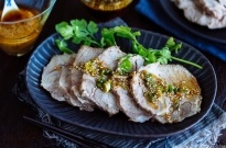 A dark plate containing sliced steamed pork topped with garlic soy sauce and garnished with cilantro.
