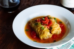 A white plate containing two cabbage rolls with tomato sauce in the tomato sauce. A wine glass and wine bottle in the back of the table.