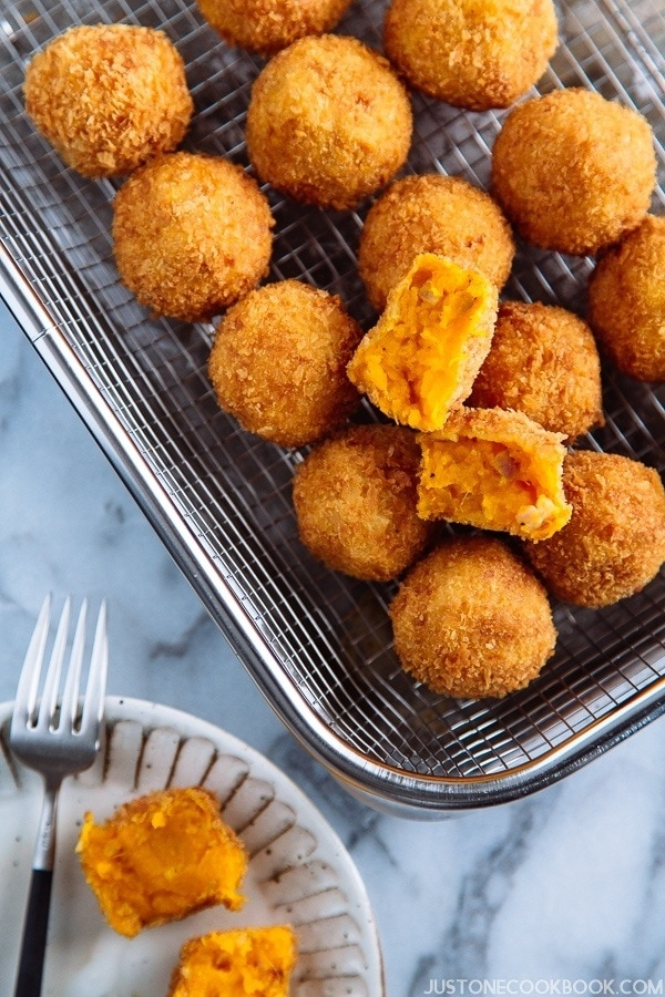 A wire rack containing small ball shape Japanese pumpkin croquettes.