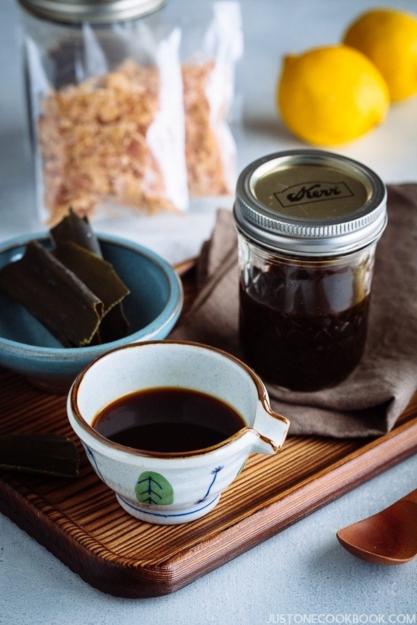 Homemade Ponzu Sauce in a small bowl and glass jar on a wooden tray.