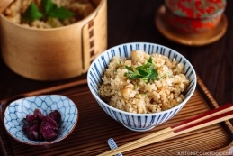 Japanese table setting with a Japanese rice bowl containing seasoned mixed rice with sweet onion, a tea cup, a small pickled dish, and a bamboo rice container.