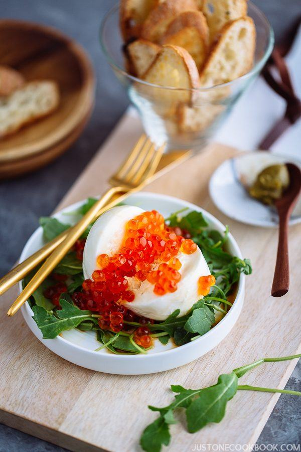 Burrata Crostini with Ikura and arugula is served on a white plate along with gold cutely.