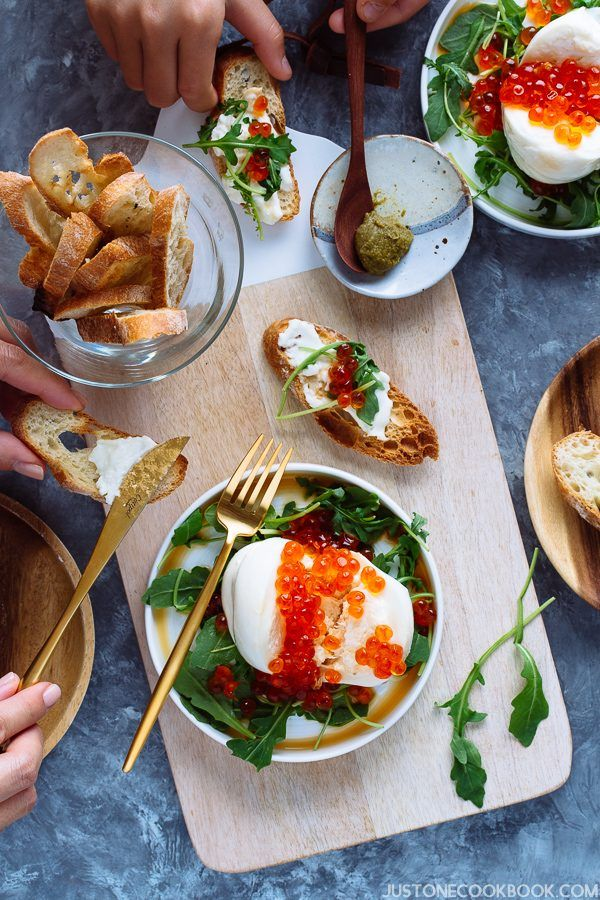 Overhead shot of tabletop with two people preparing burrata cheese and ikura crostini