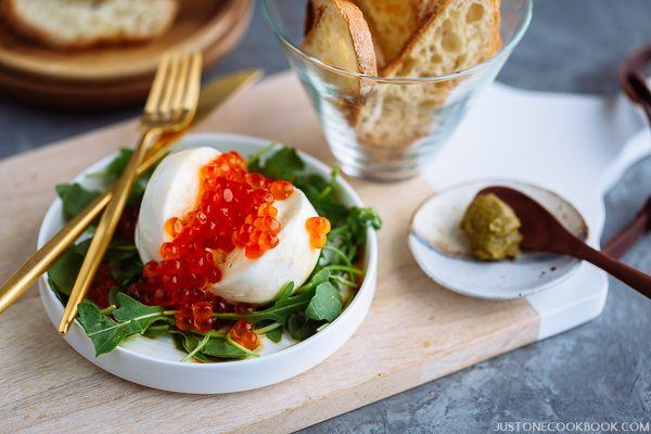 On a wooden board, there is a small white dish containing burrata cheese, ikura, and arugula, served with crostini.