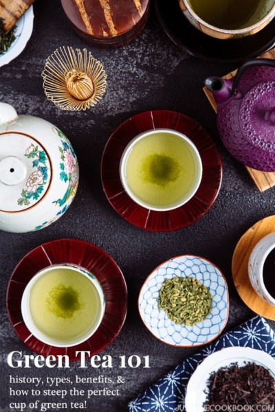 Japanese tea cups and pots along with different types of teas on the table.