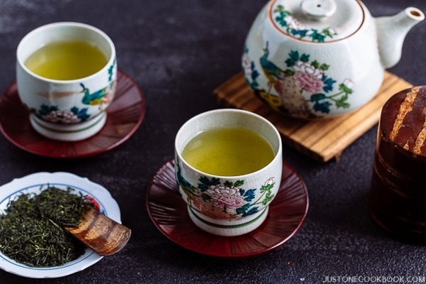 Green tea in cups and a pot behind.