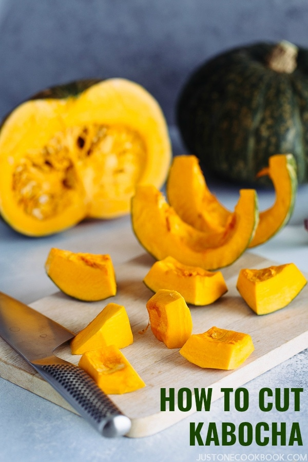 A whole Kabocha squash is being peeled and cut into cubes on a cutting board.