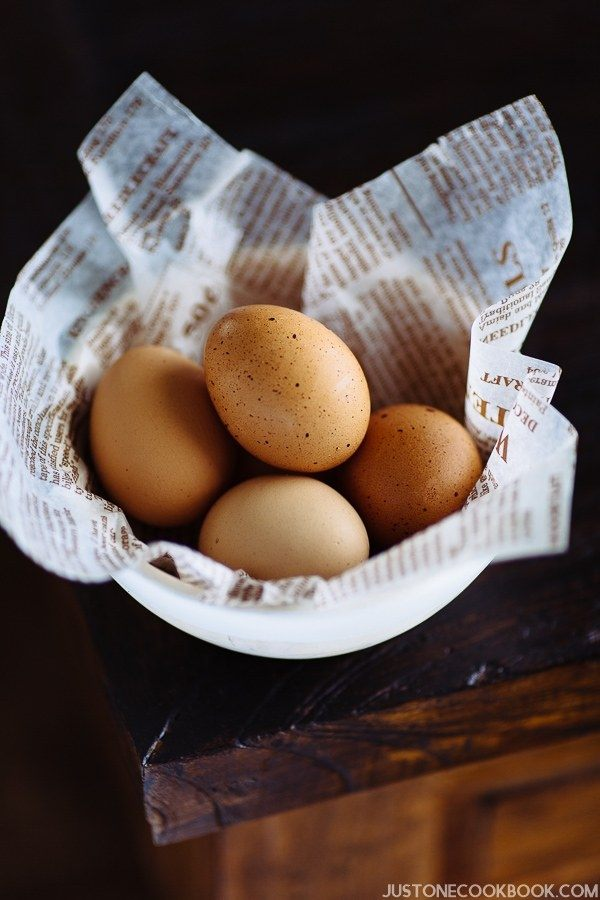 A white wooden bowl containing pasteurized brown eggs.