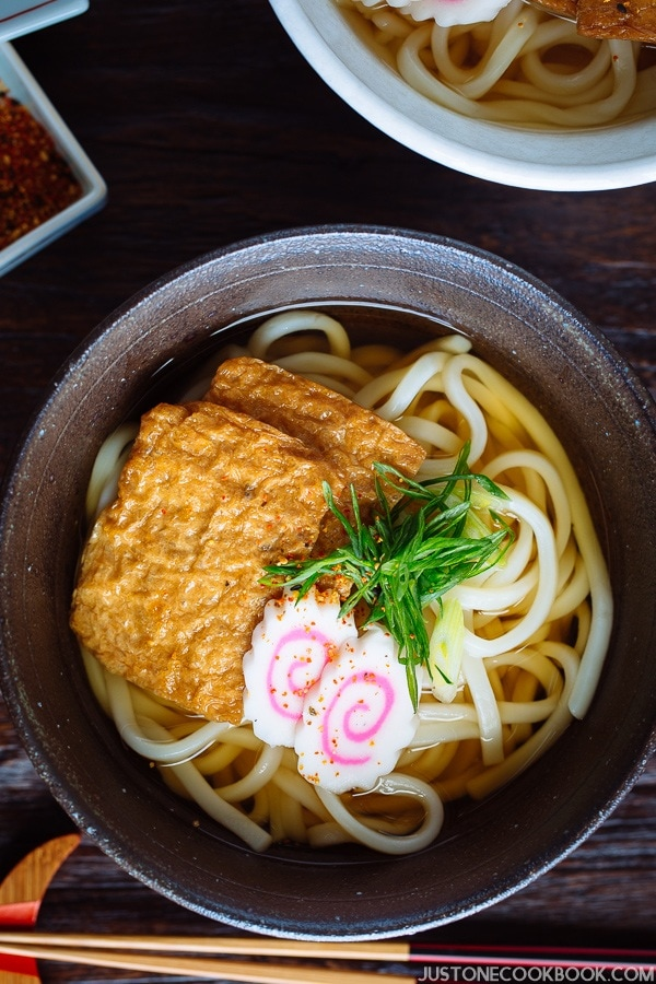 A dark bowl containing udon noodles in dashi broth topped with deep fried tofu, fish cake, green onion, and sprinkle of shichimi togarashi.