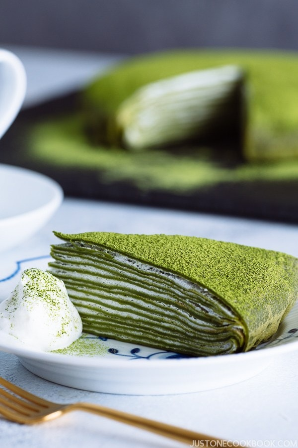 A slice of matcha mille crepe on a Royal Copenhagen plate with fresh whipped cream on side.