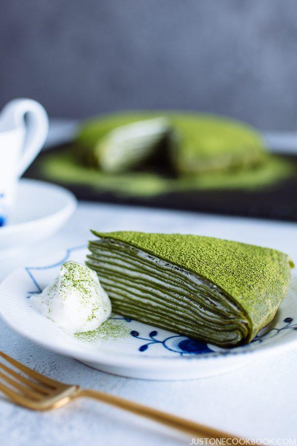 A slice of matcha mille crepe cake on a Royal Copenhagen plate. The whole cake in the back of the plate.