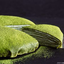 A slice of matcha mille crepe cake taken out of the whole cake.