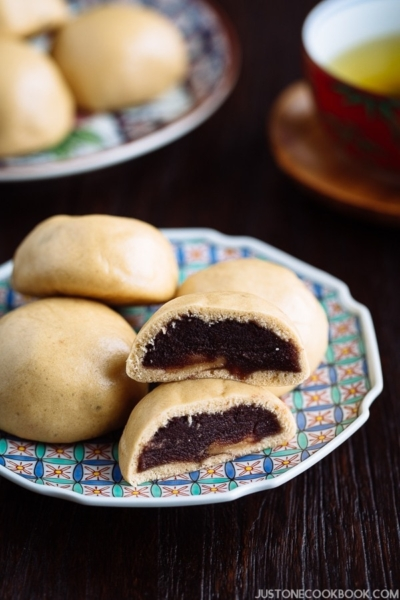 A colorful Japanese plate containing manju filled with red bean paste.