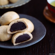 A dark Japanese plate containing manju filled with red bean paste served with green tea.