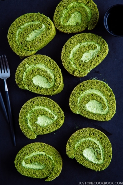 Slices of matcha roll cakes on the black cutting board.