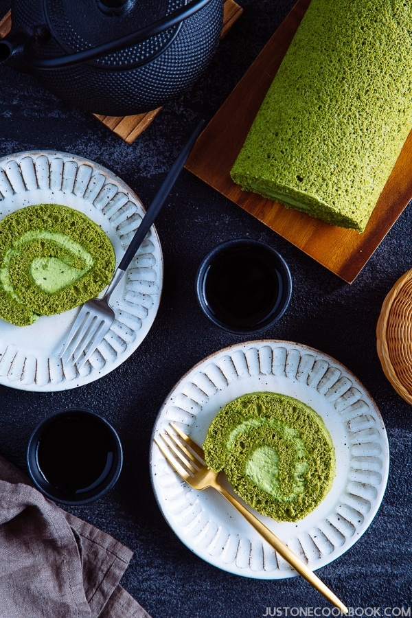 A slice of matcha swiss roll on the white plates with uncut roll cake on the back.