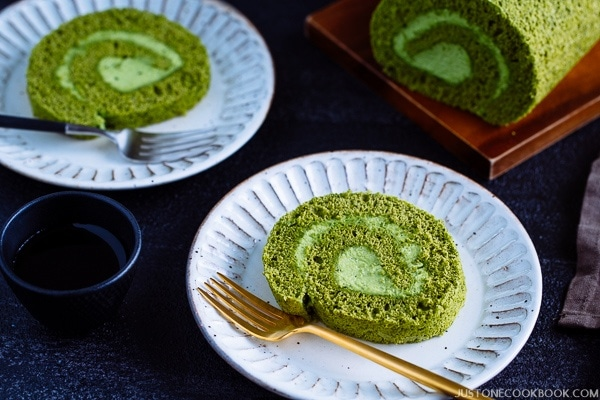 A slice of matcha swiss roll on the white plate along with gold color folk.