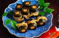Japanese blue plate containing Salmon Kombu Roll garnished with green leaves.
