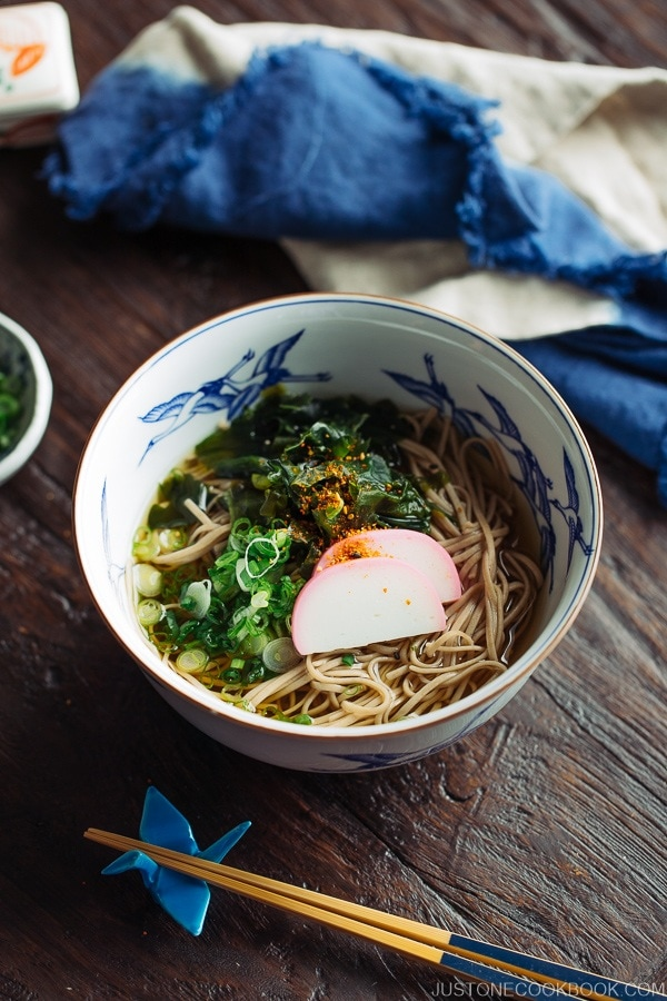 Toshikoshi Soba Noodle Soup with fish cake and wakame seaweed in a Japanese bowl.