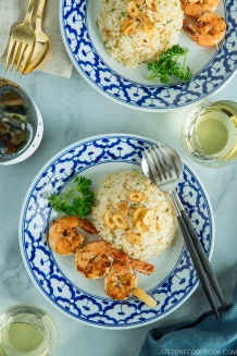 A blue and white plate containing Japanese Garlic Fried Rice topped with garlic chips and grilled shrimp skewer.