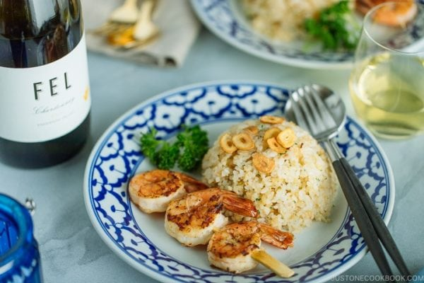 A blue and white plate containing Japanese Garlic Fried Rice topped with garlic chips and grilled shrimp skewer. Served with a glass of wine.