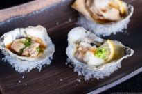 Dark Japanese plate containing Grilled Oysters with 3 kinds of garnish and Ponzu Sauce