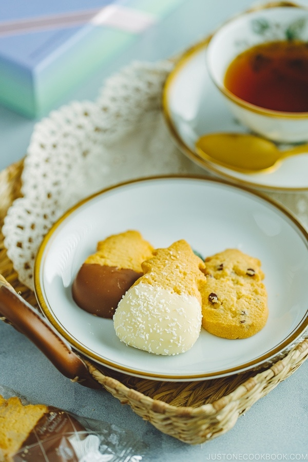 Tea in a cup and a gold rim dish containing various cookies from Honolulu Cookie Company.