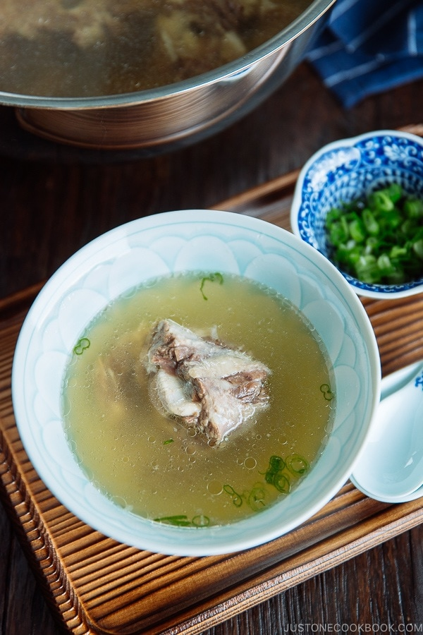 Piping hot oxtail broth in a Japanese bowl topped with green onions.