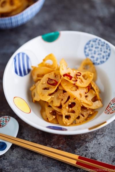A round colorful Japanese bowl containing Kinpira Renkon (Japanese Lotus Root Stir Fry).