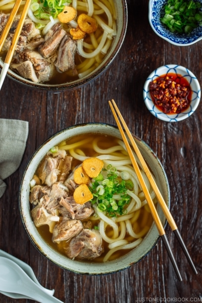A large bowl of Oxtail Udon topped with tender meat, fried garlic, and green onion.