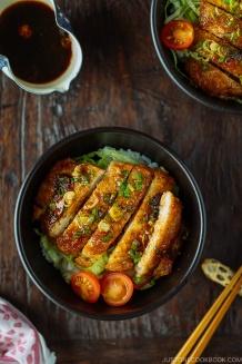 A black bowl containing Teriyaki Pork over steamed rice drizzled with homemade teriyaki glaze.