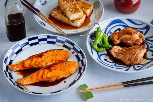 Teriyaki Tofu, Teriyaki Salmon, and Teriyaki Chicken served each on a Japanese plate seasoned with homemade Teriyaki Sauce.