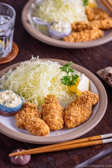 Kaki Fry (Japanese Panko Fried Oysters) served with tartar sauce and shredded cabbage on the white plate.