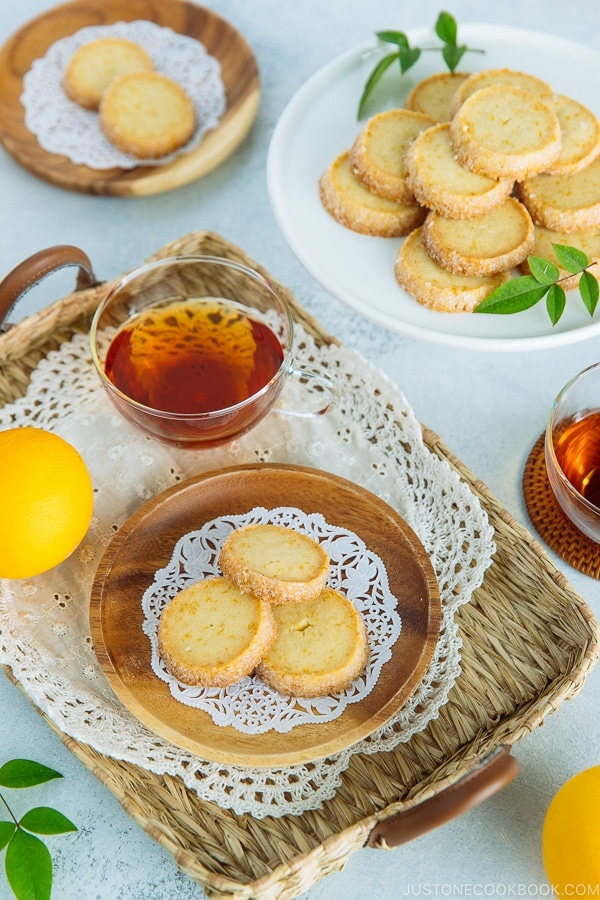 A wooden plate containing Meyer Lemon Sables and a cake stand behind holding more sables.