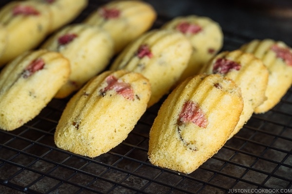 Cherry Blossom Madeleines laid staggered on a wire rack.