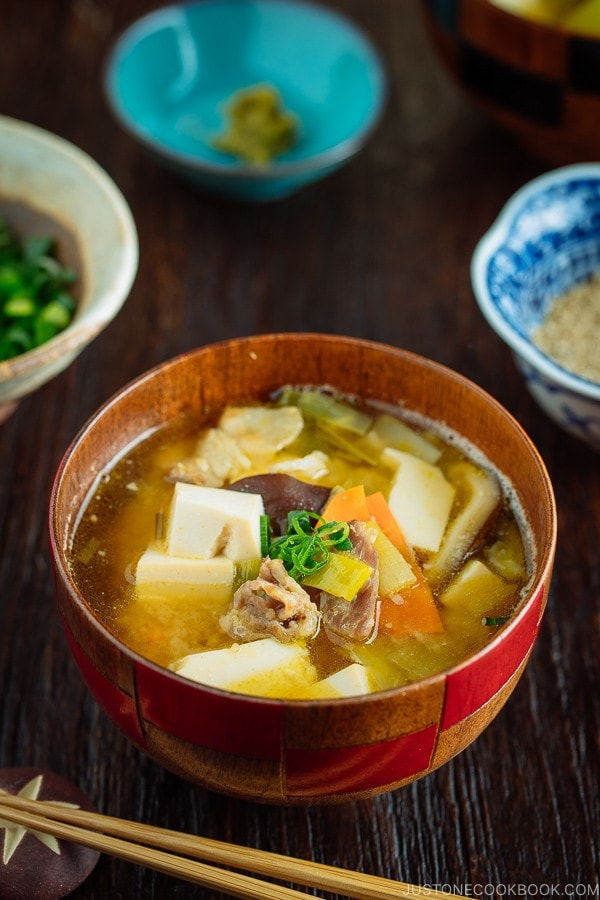 Pork belly and vegetable miso soup in a wooden bowl.