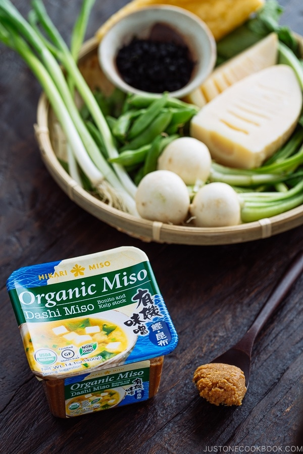 "A tub of ""Organic Miso - Dashi Miso"" by Hikari Miso. A bamboo basket behind containing vegetables."