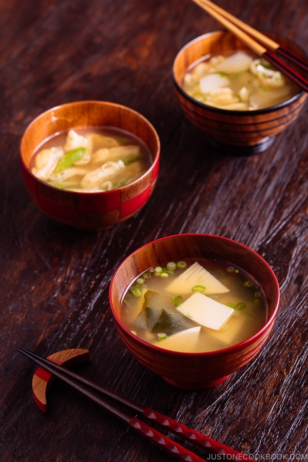 Three kinds of vegetable miso soups, each served in a wooden bowl.