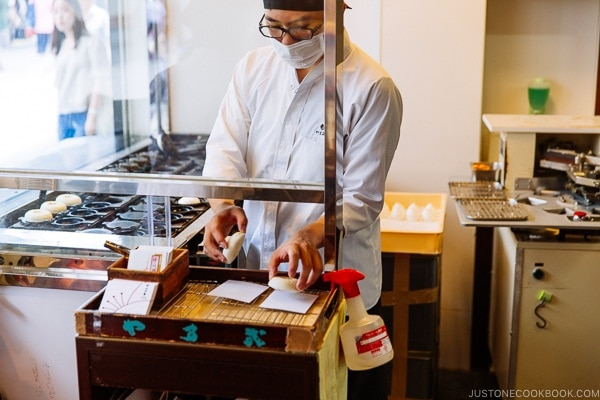 Worker placing umegaemochi on paper - Dazaifu speciality sweet - Fukuoka Travel Guide | justonecookbook.com