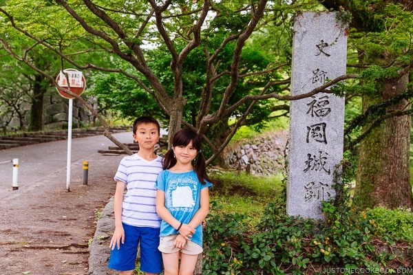 children standing next to Fukuoka Castle Ruin sign - Fukuoka Travel Guide | justonecookbook.com
