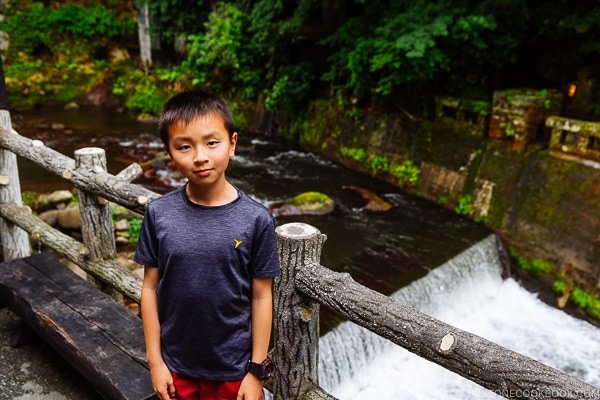 boy standing next to river bank Kurokawa Onsen Travel Guide | justonecookbook.com