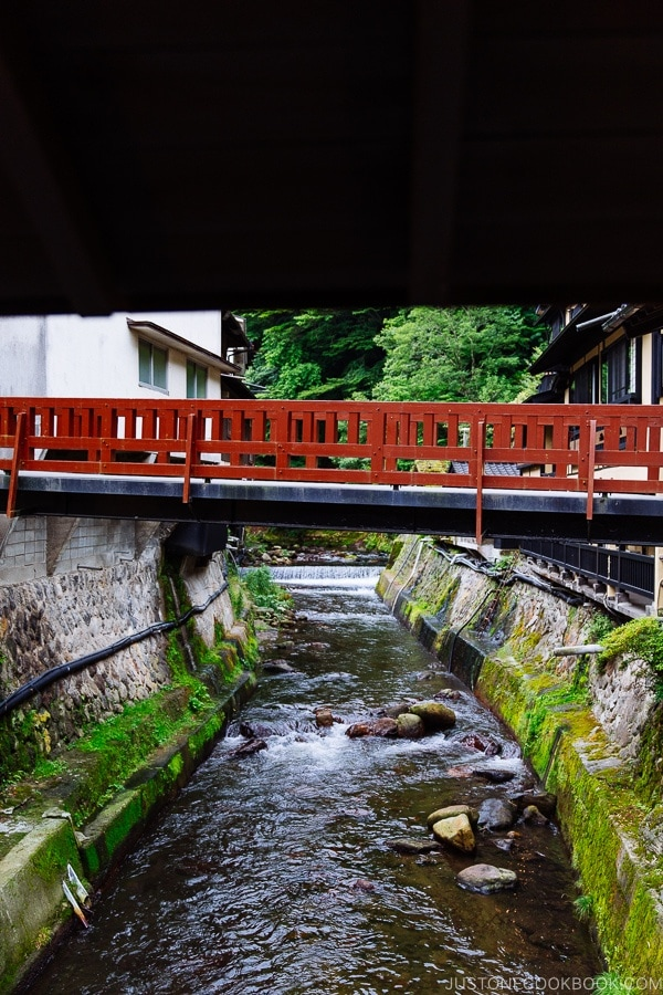 view of red pedestrian bridge at Shinmei-kan 山の宿 新明館 Kurokawa Onsen Travel Guide | justonecookbook.com