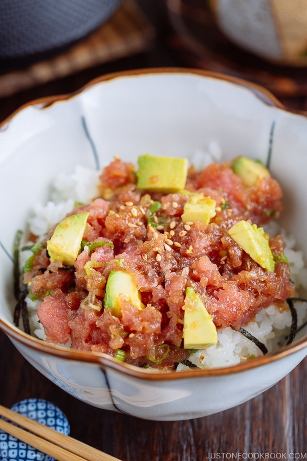A Japanese bowl containing avocado and negitoro (fatty tuna) on top of steamed rice.