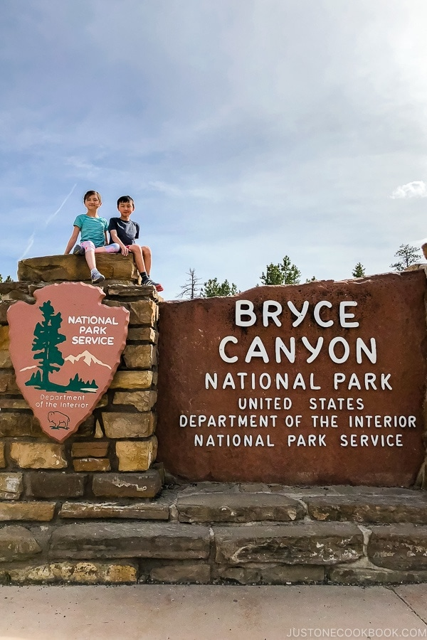 children on top of Bryce Canyon National Park sign - Bryce Canyon National Park Travel Guide | justonecookbook.com